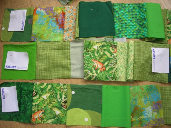 Fabric squares of various green patterns cut and sewn into strips for handmade quilt.