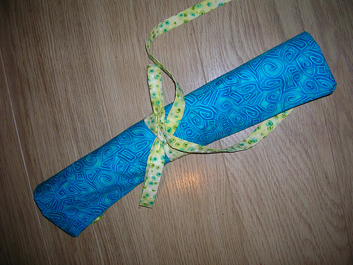 Handmade sewn knitting needle roll in turquoise and yellow fabric.