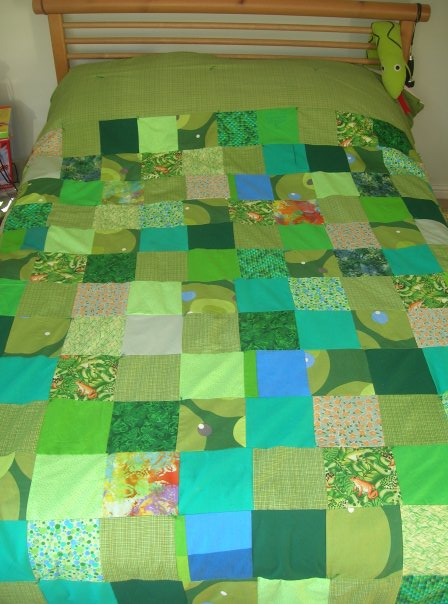 Handmade patchwork quilt in green.