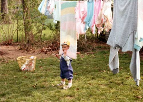 Toddler with blanket on clothesline. Pennsylvania, 1983 or 1984