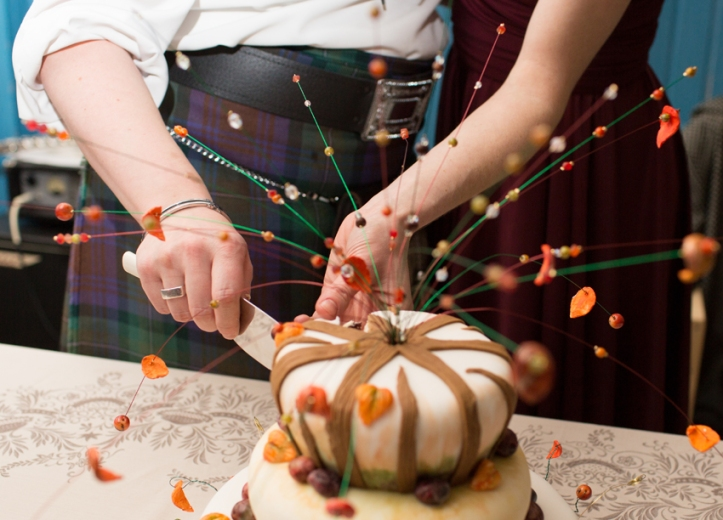 Cutting Thanksgiving wedding cake by Kat Goldin Images