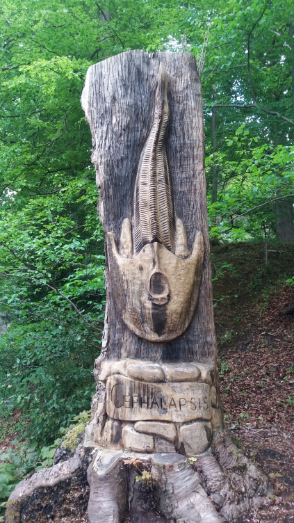 Carved tree trunk totem with fossil in Mine Wood Bridge of Allan Scotland